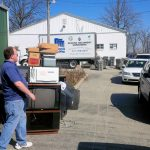 Man standing by TVs and shredding truck